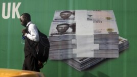 A man walks past a promotional banner showing a photograph of a pile of Nigerian naira along a road in Lagos November 24, 2010.