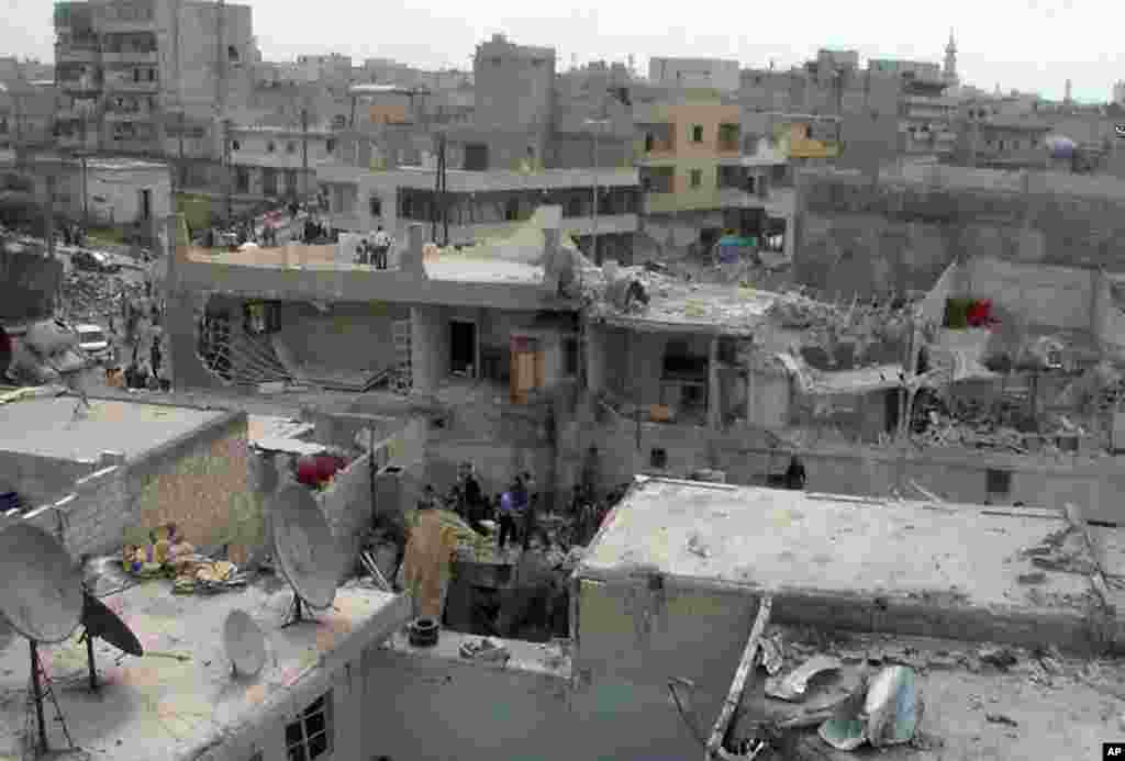 This citizen journalism image provided by AMC shows people on the top of houses that were damaged by an airstrike, Aleppo, Syria, April 15, 2013.