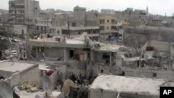 阿勒颇居民4月15日在遭到政府军空袭破坏的建筑物屋顶上