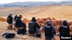 攝影師和記者坐在敘土邊境的一座山丘上觀看科巴尼的戰鬥。(2014年10月15日)