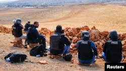 2014年10月15日,攝影師和記者坐在敘土邊境的一座山丘上觀看科巴尼的戰鬥。