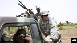 Malian troops and their U.S. Special Forces instructor await the start of a live-fire drill in Kita, Mali, during a joint training exercise with a unit of elite Malian troops, May 10, 2010.