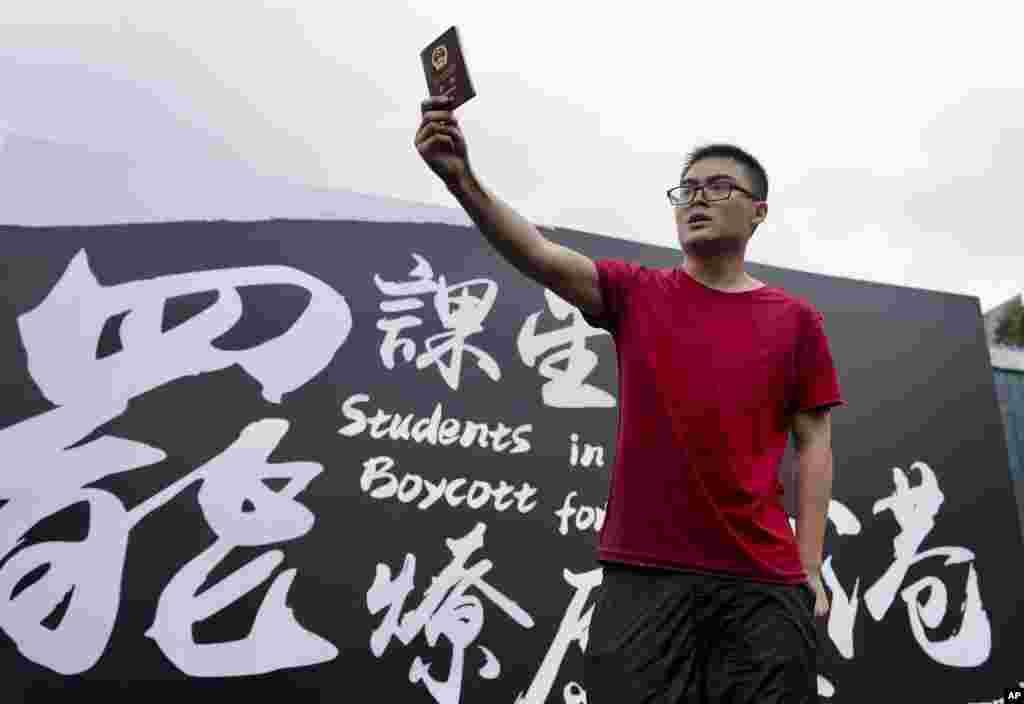 在抗议者在香港中文大学举行罢课集会之际,一位来自中国大陆的学生高举自己的中国护照向抗议者示威。(2019年9月2日)