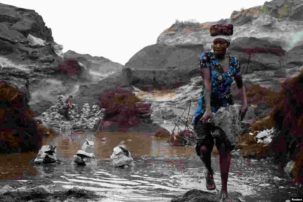 A woman carries stones in Pissy informal granite quarry in Ouagadougou, Burkina Faso.
