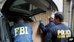 在旧金山中国城,美国联邦调查局特工对一个帮会组织进行搜查后,将证据装箱运走。