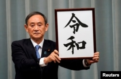 Japan's Chief Cabinet Secretary Yoshihide Suga unveils 'Reiwa' as the new era name at the prime minister's office in Tokyo, Japan, April 1, 2019.