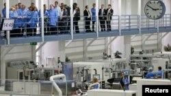 Kanselir Jerman Angela Merkel dan Kepala Eksekutif Grup Industri Jerman, Siemens, Joe Kaeser, menyaksikan ruangan produksi saat berkunjung di pabrik elekteronik Siemens di Amberg, Jerman (23/2). Jutaan pekerja industri Jerman akan mendapat kenaikan gaji 3,4 persen tahun ini.
