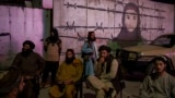 Taliban members sit in front of a mural depicting a woman behind barbed wire in Kabul, Afghanistan, Sept. 21, 2021.