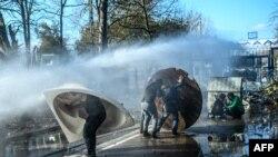Grčka policija vodenim topovima pokušava da spreči migrante da probiju ogradu na granici Turske i Grčke u provinciji Edirne, 7. marta 2020.