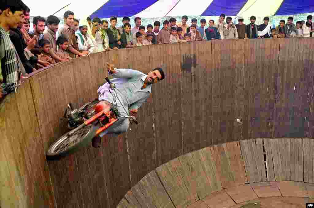 """Afganistanac, vozač akrobata na """"zidu smrti"""" zabavlja građane Jalalabada, Afganistan."""