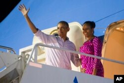 FILE - President Barack Obama, left, and first lady Michelle Obama wave as they board Air Force One to depart from Joint Base Pearl Harbor-Hickam at the end of their family vacation, Jan. 2, 2016, in Honolulu, Hawaii.