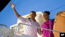 Presiden Barack Obama, kiri, dan ibu negara Michelle Obama saat menaiki pesawat Air Force One untuk kembali ke Washington dari Pangkalan Gabungan Pearl Harbor-Hickam setelah libur natal, 2 Januari 2016, di Honolulu, Hawaii.