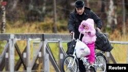 Un homme et sa fille à la station frontalière russe de Storskog dans le nord de la Norvège le 13 Octobre 2015. La loi norvégienne oblige Les migrants à voyager en vélo. Source: Reuters