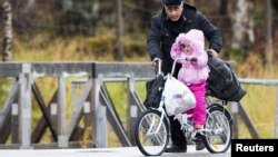 A man pushes a girl across the border from Russia to Norway on a bicycle with flat tires at the Storskog border station in northern Norway, Oct. 13, 2015. Migrants entering Norway via Russia must travel by bicycle to comply with a Russian law barring trav