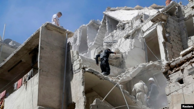 FILE - Residents look for survivors among the debris and damage after what activists said was shelling from forces loyal to Syria's President Bashar al-Assad at Al-Kallaseh in Aleppo, Syria.