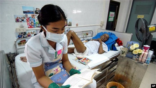 A nurse, wearing protective mask and gloves reads to a HIV/AIDS patient at the Phra Baht Nam Phu AIDS hospice near Lopburi, Thailand (File)