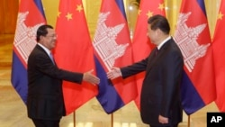 Cambodia's Prime Minister Hun Sen (L) stretches to shake hands with China's President Xi Jinping before a meeting at the Great Hall of the People in Beijing, November 7, 2014. REUTERS/Jason Lee/POOL