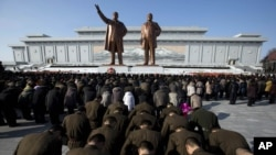 North Korean soldiers bow before the statues of late leaders Kim Il Sung, left, and Kim Jong Il, right, at Mansu Hill in Pyongyang, North Korea, December 17, 2012.
