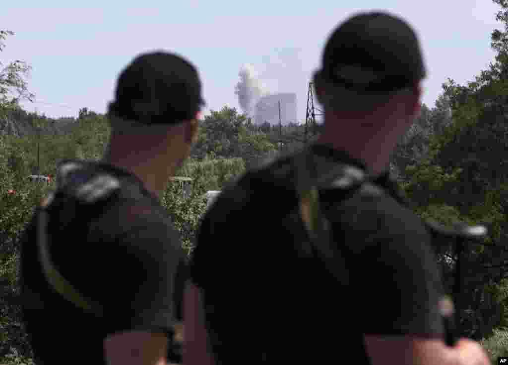 Self-proclaimed Donetsk People's Republic policemen watch shelling in Shakhtarsk, Donetsk region, eastern Ukraine, July 28, 2014.