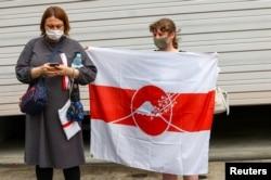 Seorang wanita Belarusia memegang bendera saat sprinter Krystsina Tsimanouskay tiba di kedutaan Polandia di Tokyo, Jepang, 2 Agustus 2021. (REUTERS/Kim Kyung-Hoon)