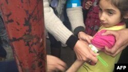 A handout picture released by UNICEF and taken Jan. 14, 2016, shows a UNICEF employee measuring the arm of a malnourished child in the besieged Syrian town of Madaya, as they assess the health situation of residents of the famine-stricken town.