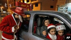 A Palestinian man dressed as Santa Claus stands near a car as he hands out Christmas presents to children in the West Bank city of Bethlehem, ahead of Christmas, 20 Dec 2010