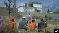 Une famille pakistanaise assistant à la destruction du complexe où vivait Ossama ben Laden et au moins 24 autres personnes, à Abbottabad. Le 26 février 2012