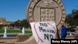 """FILE - In this 2014 photo, aTexas Tech student drape a bed sheet with the message """"No Means No"""" over the university's seal at the Lubbock, Texas campus."""