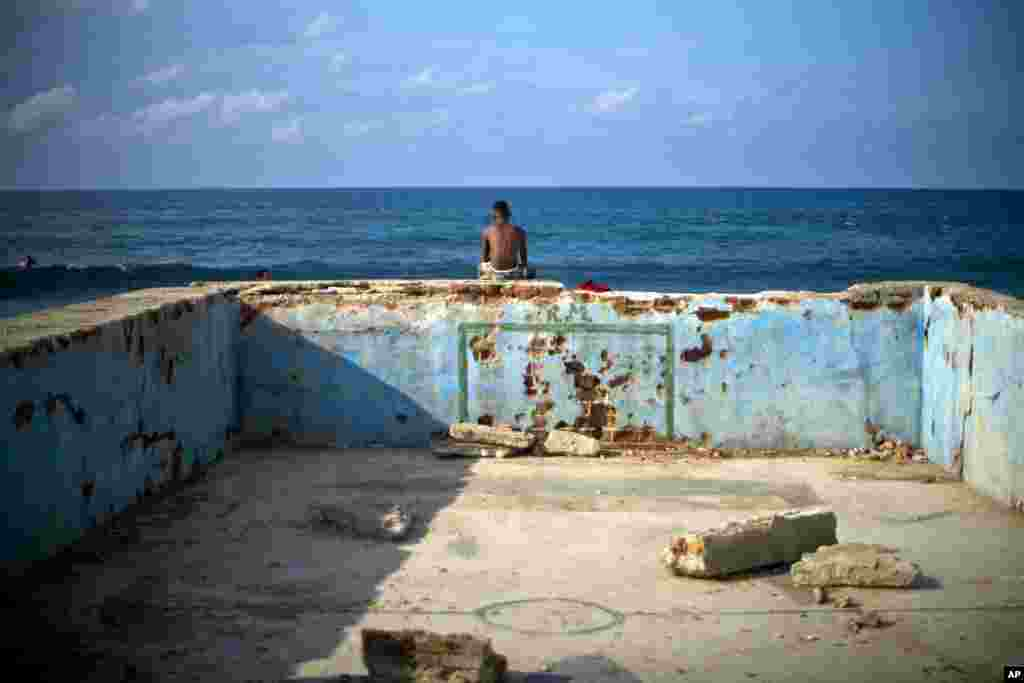 A young man looks at the sea sitting on the wall of an old abandoned pool in Cojimar, Cuba.