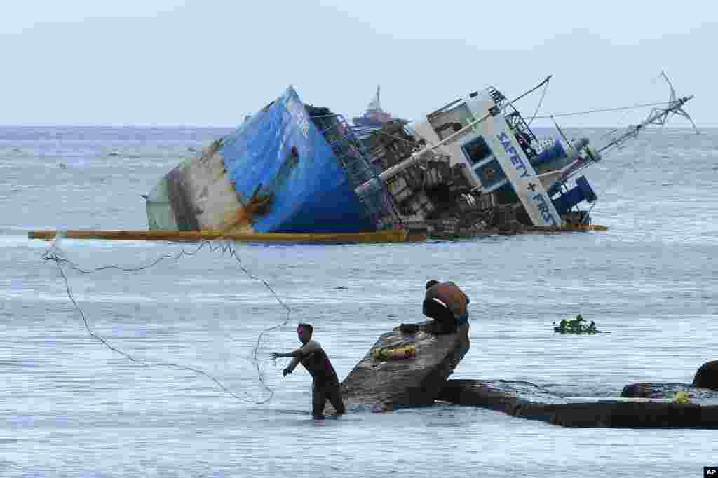 A fisherman throws his net beside the half-submerged M/V Palawan Pearl after it collided with a Cyprus-flagged BKM 104 dredger in Manila bay, Philippines.