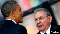 U.S. President Barack Obama greets Cuban President Raul Castro at a memorial service for late South African President Nelson Mandela, Johannesburg, Dec. 10, 2013.