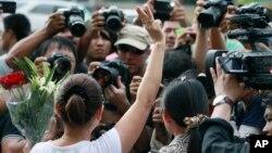 """Seorang perempuan mengacungkan salam tiga jari yang diambil dari film """"The Hunger Games"""" dalam demonstrasi anti-kudeta militer di Bangkok, Thailand (4/6). (AP/Wason Wanichakorn)"""