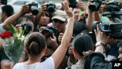 """A woman flashes a three-fingered salute borrowed from """"The Hunger Games"""" during an anti-coup demonstration outside the Australian Embassy in Bangkok, Thailand Wednesday, June 4 , 2014"""