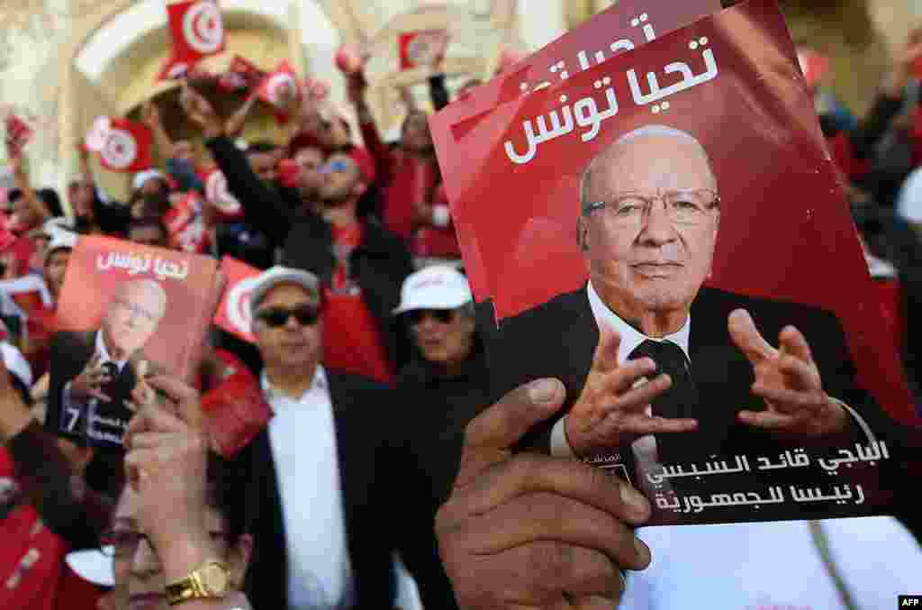 Supporters of Tunisian presidential candidate Beji Caid Essebsi (portrait), shout slogans and wave flags on Bourguiba Avenue in the capital, Tunis, during an election campaign ahead of the upcoming presidential elections on Nov. 23.