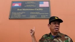 Cambodia's Ministry of Defense spokesperson Chhun Socheat shows a sign donated by the US during a government organized media tour to the Ream naval base in Preah Sihanouk province on July 26, 2019.