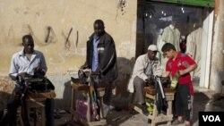 Pekerja migran dari Afrika menawarkan jasa permak pakaian di pinggiran jalan kota Benghazi, Libya.