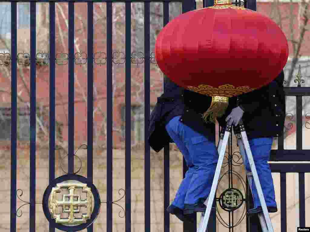2013年2月7日,在中国北京,工人们在一处公寓楼大门外张挂大红灯笼,准备迎接农历新年的到来。