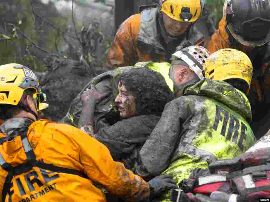 Emergency personnel carry a woman rescued from a collapsed house after a mudslide in Montecito, California, Jan. 9, 2018.