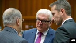 German Foreign Minister Frank-Walter Steinmeier, center, speaks with Cypriot Foreign Minister Ioannis Kasoulides, left, and Danish Foreign Minister Kristian Jensen, right, during a meeting of EU foreign ministers at the EU Council building in Brussels, Nov. 14, 2016.