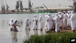 FILE - Members of the Sabean Mandaeans, a pre-Christian sect that follows the teachings of John the Baptist, take part in a bathing ritual during the Baptism Festival, on the banks of the Shatt al-Arab waterway in Basra, 340 miles (550 kilometers) southeast of Baghdad, Iraq, May 20, 2015.