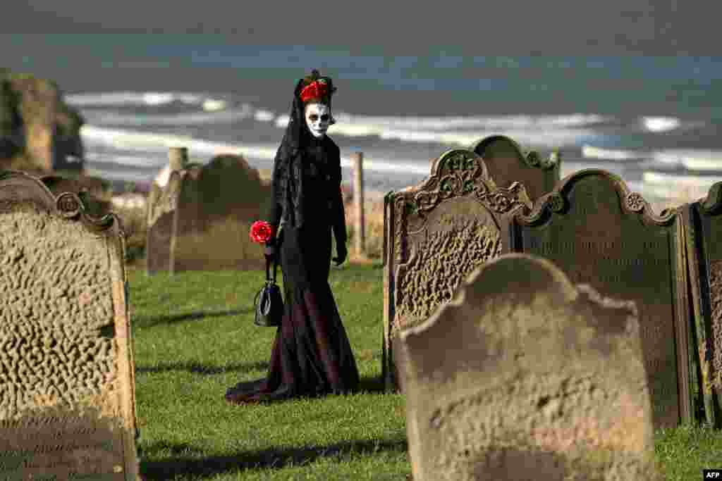 A participant in costume walks between the gravestones in St. Mary's church graveyard during the biannual 'Whitby Goth Weekend' festival in Whitby, northern England.