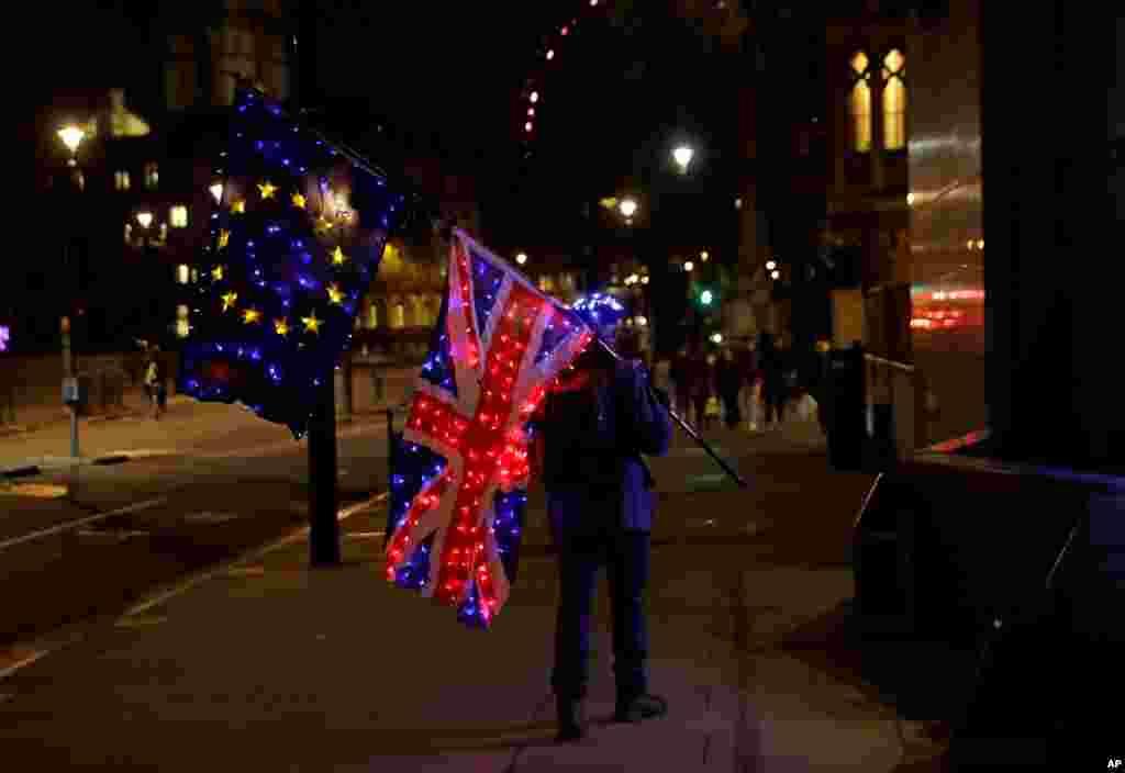 영국과 유럽연합(EU)의 영국 EU 탈퇴후 무역 협정이 논의되고 있는 런던의 컨퍼런스 센터 앞에서 친EU 시위자가 영국 국기를 들고 서있다.