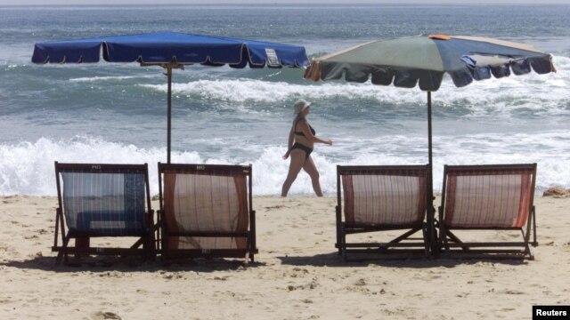 Du khách nước ngoài đi bộ dọc bãi biển ở Đà Nẵng.