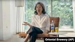 """South Korean actor Youn Yuh-jung """"Minari"""" sits in the beer company Oriental Brewery's latest advertising campaign. (Oriental Brewery via AP)"""