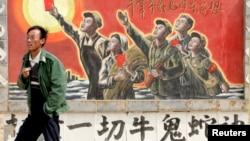 一名男子走過寧夏銀川街頭郊區的一處描寫中國文革的宣傳畫。(2007年4月25日)