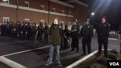 Un manifestante en máscara de Anonymus posa frente a la policía de Ferguson. Él fue uno de los arrestados del miércoles. (Ayesha Tanzeem/VOA)