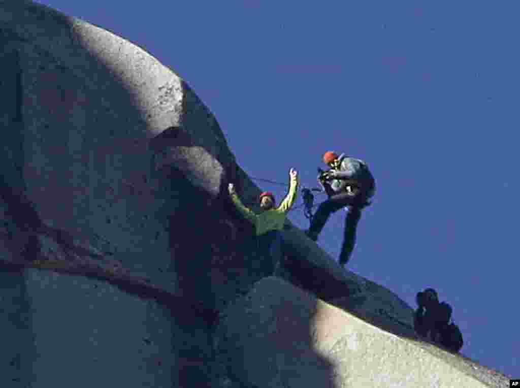 Tommy Caldwell (atas) mengangkat tangannya setelah berhasil mencapai puncak El Capitan di Taman Nasional Yosemite, California (14/1).