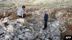 Syrian men stand inside crater where they said Scud missile landed December 13, 2012