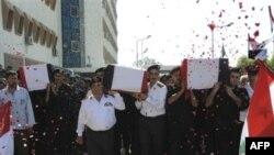 Cảnh sát Syria khiêng quan tài của các nhân viên an ninh thiệt mạng trong vụ thảm sát tại thành phố Jir al-Shughour ở tây nam nước này