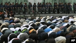 Thai police officers look at Thai-Muslim demonstrators conducting afternoon prayers outside a shopping mall where the office of Google Thailand is located, during a demonstration against a video produced in the United States that denigrates the Prophet Mu